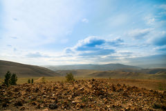 白色,蓬松云彩漂浮在青山的蓝天的和谷 库存照片