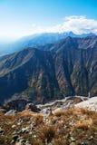 白色,蓬松云彩漂浮在青山的蓝天的和谷 图库摄影