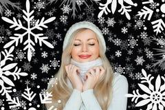 白色,被编织的帽子和围巾的美丽的白肤金发的妇女 在与雪花的黑背景 冬天舒适 库存照片