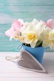 白色水仙和桃红色郁金香在桶有装饰心脏的 库存图片