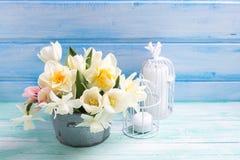 白色黄水仙和郁金香花在桶和蜡烛在12月 库存图片