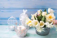 白色黄水仙和郁金香花在桶和蜡烛在tu 免版税库存照片