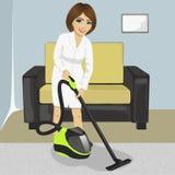 白色浴巾清洁地毯的少妇有吸尘器的在家 库存照片