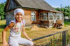 白色围巾的小镇静女孩反对近的农村房子 免版税库存图片