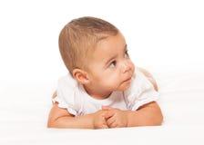 白色紧身衣裤的好奇看起来的非洲婴孩 免版税库存照片