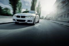 白色BMW 3系列F30汽车在柏油路驾驶在夏天白天 免版税库存照片