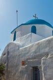 白色chuch惊人的看法与蓝色屋顶的在Parakia,帕罗斯岛海岛,希腊镇  免版税图库摄影