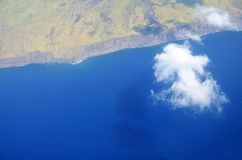 白色cloudscape补丁在大海的 库存图片
