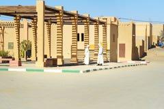 白色djellaba的两个摩洛哥人在街道上谈话在Merzouga村庄,摩洛哥 库存图片