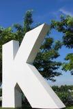 白色K在天空背景中 免版税库存图片