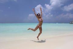 白色Maldivian海滩的跳跃的女孩 免版税库存照片