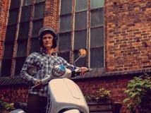 白色moto滑行车的一个人在老镇 免版税库存照片