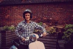 白色moto滑行车的一个人在老镇 库存图片