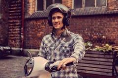 白色moto滑行车的一个人在老镇 库存照片