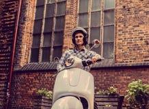 白色moto滑行车的一个人在老镇 免版税库存图片