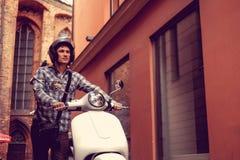 白色moto滑行车的一个人在老镇 免版税图库摄影