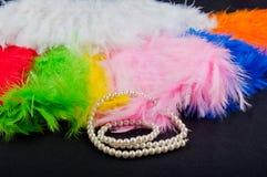 白色perl项链在黑背景放置在五颜六色的折叠的爱好者附近 免版税库存照片