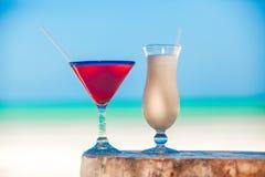 白色pina colada和红色玛格丽塔酒在海滩 免版税库存照片