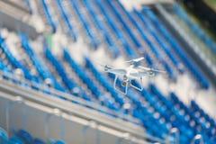 白色quadcopter飞行在橄榄球场并且拍摄录影 在蓝色位子背景的寄生虫在体育场的 库存图片