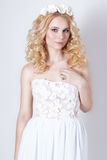 白色sundress薄绢和卷毛的美丽的可爱的柔和的典雅的年轻白肤金发的妇女和花花圈在她的头发的 库存图片