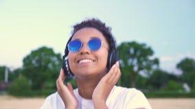 白色T恤和蓝色太阳镜的两种人种的非裔美国人的女孩少年年轻女人走听到在无线的音乐的他 影视素材