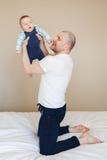 白色T恤杉和黑牛仔裤的白种人父亲坐床户内,举行占去新出生的小儿子 库存图片