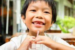 白色T恤杉的一个聪明的男孩微笑着与他的断的牙 免版税库存照片