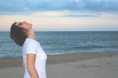 白色T恤杉的俏丽的女孩在海滩和查寻 免版税库存照片