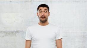 白色T恤杉的害怕的人在墙壁背景 免版税库存图片