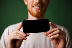 白色T恤杉的播种的照片红头发人有胡子的人做一张照片 图库摄影