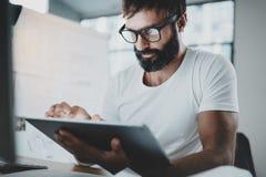 白色T恤杉的有胡子的人与便携式的电子赞成片剂计算机一起使用在现代lightful办公室 水平 免版税图库摄影