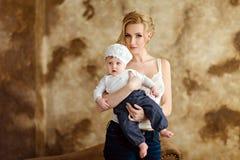 白色T恤杉的美丽的亭亭玉立的白肤金发的妈妈拿着一个小女孩我 免版税库存照片