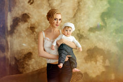 白色T恤杉的美丽的亭亭玉立的白肤金发的妈妈拿着一个小女孩我 免版税库存图片