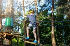 白色T恤杉的运动,年轻,逗人喜爱的男孩在公园在冒险绳索公园盔甲的和安全设备花费他的时间 免版税库存照片