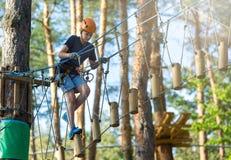 白色T恤杉的运动,年轻,逗人喜爱的男孩在公园在冒险绳索公园盔甲的和安全设备花费他的时间 图库摄影
