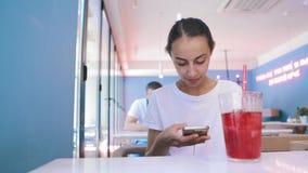 白色T恤的俏丽的年轻被晒黑的妇女在咖啡馆坐,并且用途打电话,看,读或者搜寻某事 股票视频