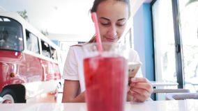 白色T恤的俏丽的年轻被晒黑的妇女在咖啡馆坐,并且用途打电话,看,读或者搜寻某事 影视素材