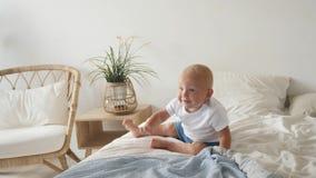 白色T恤的孩子和蓝色短裤在床上使用了 股票视频