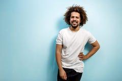 白色T恤的微笑的curly-headed人用在臀部的一只手 有正面外型的一个脾气随和的人 幸福 免版税库存照片