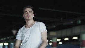 白色T恤的愉快的自信人离开站立在地下停车处的太阳镜 股票视频