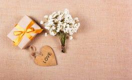 白花、心脏和礼物 浪漫概念 背景和纹理 库存图片