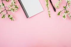 白花、笔记本和笔框架在桃红色背景 平的位置,顶视图 博客作者或自由职业者书桌工作区 库存照片