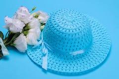 白花南北美洲香草和女性蓝色帽子在明亮的蓝色背景 免版税库存图片