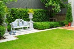 白花在一条白色长凳把枕在庭院里 库存图片