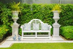 白花在一条白色长凳把枕在庭院里 免版税库存照片