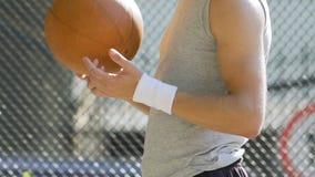 白英俊的在手指,夏天活动,平衡的人转动的篮子球 影视素材