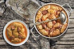 白菜卷肉在不锈的调味汁罐和瓷板材烹调和服务的劳斯在老庭院表上设置了 免版税库存图片