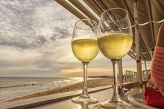 白葡萄酒俯视与日落的杯海滩 免版税库存图片