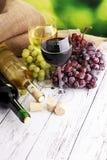 白葡萄酒和红葡萄酒在一块玻璃用秋天葡萄,白色woode 免版税库存照片