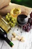 白葡萄酒和红葡萄酒在一块玻璃用秋天葡萄,白色woode 免版税图库摄影